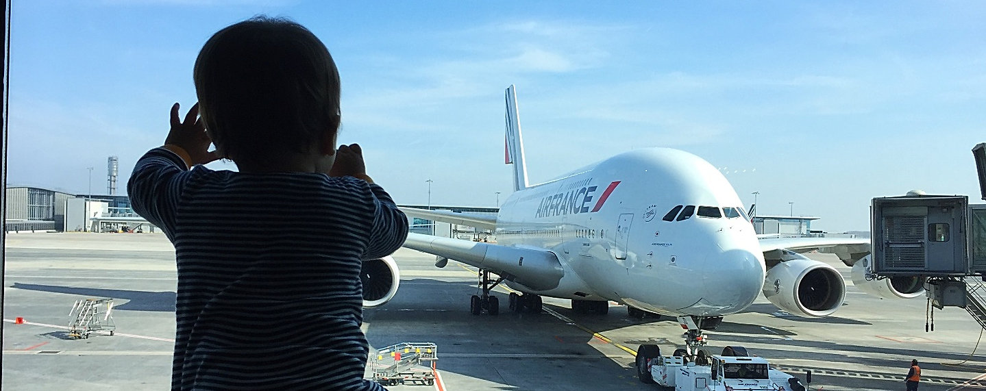 Our baby son looking out on an airplane through the windiw at an airport