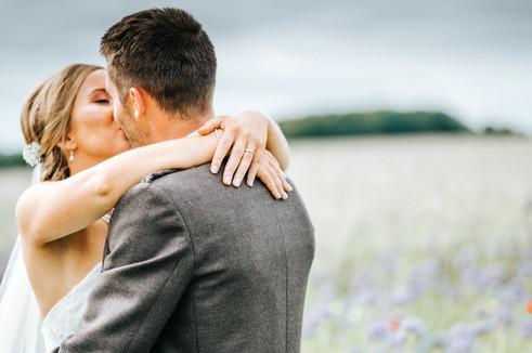 Bride & Groom Kissing in a field of wild flowers