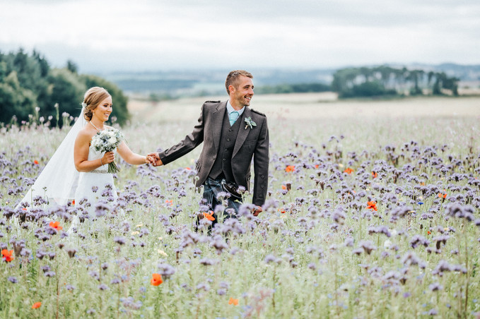 Bride & Groom walking through a field of wild flowers