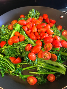 broccolini and cherry tomatoes sauteeing in olive oil