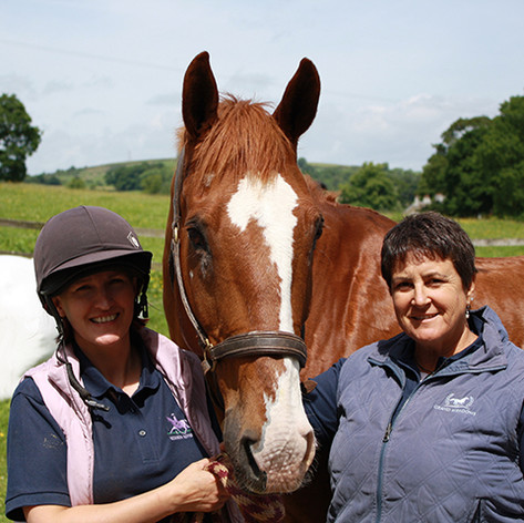 Susan Peacock standing with a student who is holding a chestnut horse.