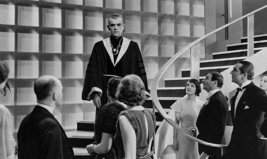 "Boris Karloff greets a room of guests in 1934's ""The Black Cat."""