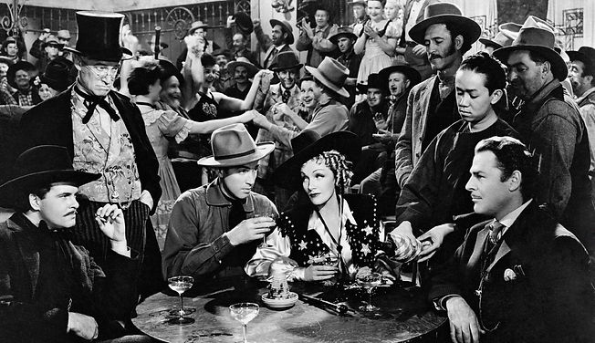 """James Stewart and Marlene Dietrich surrounded by onlookers in """"Destry Rides Again."""""""