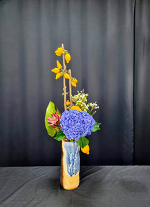 Fox face, hydrangea, wax flower, leucadendron, monstera, in ceramic vase.