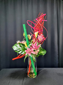 Bamboo, mitsumata and bamboo strips structure painted red, lily, monstera, in clear glass vase.