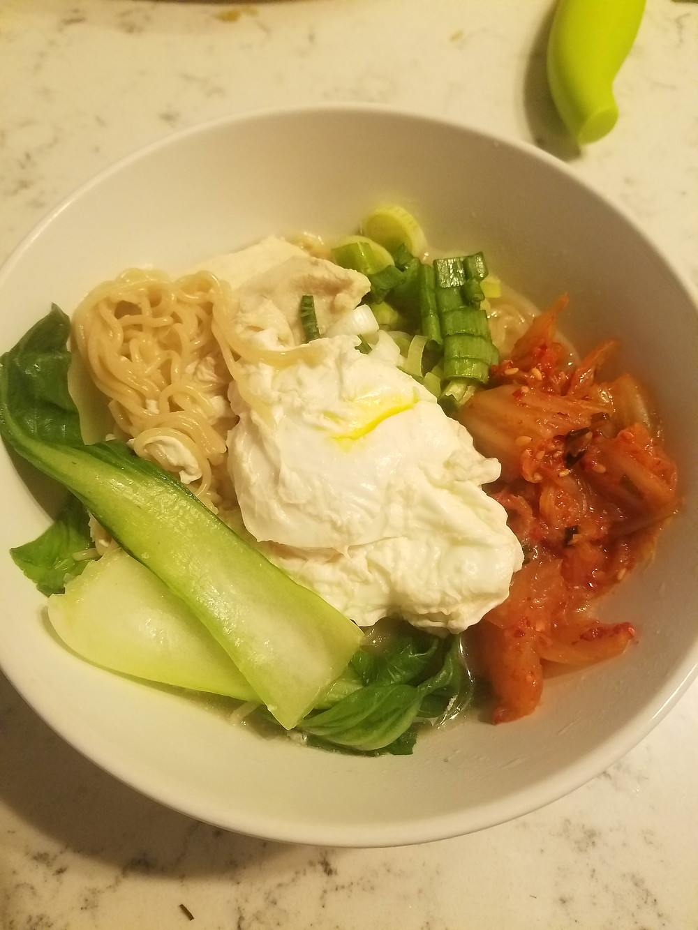 Brown rice ramen with baby bok choy, chicken, kimchi, and a runny egg