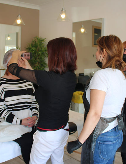 Client in a salon, surounded by two technicians