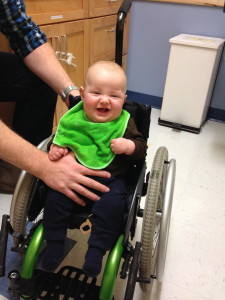 Trying out big brother's wheelchair while waiting for doctors to drop in… It's legit; really, the four month old can't walk either!