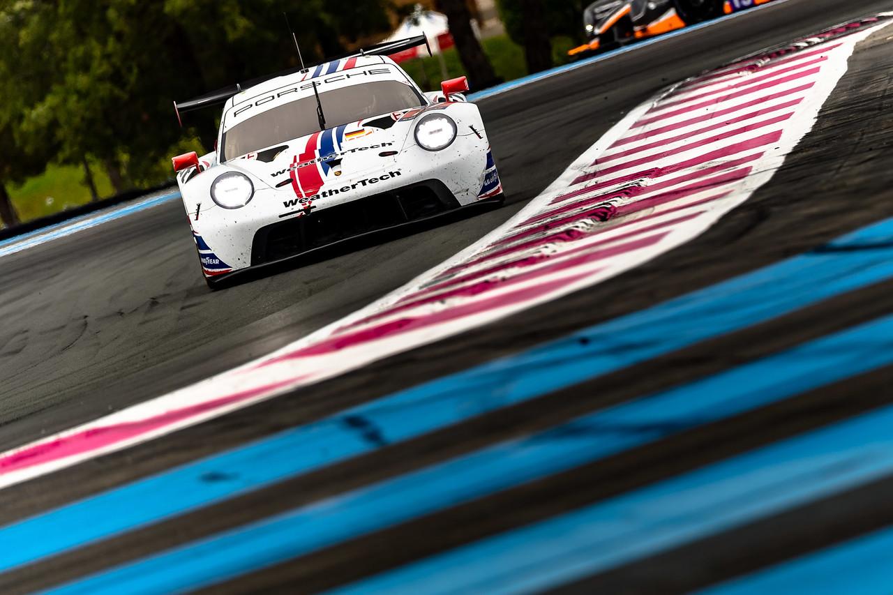 Porsche racing around a curve.