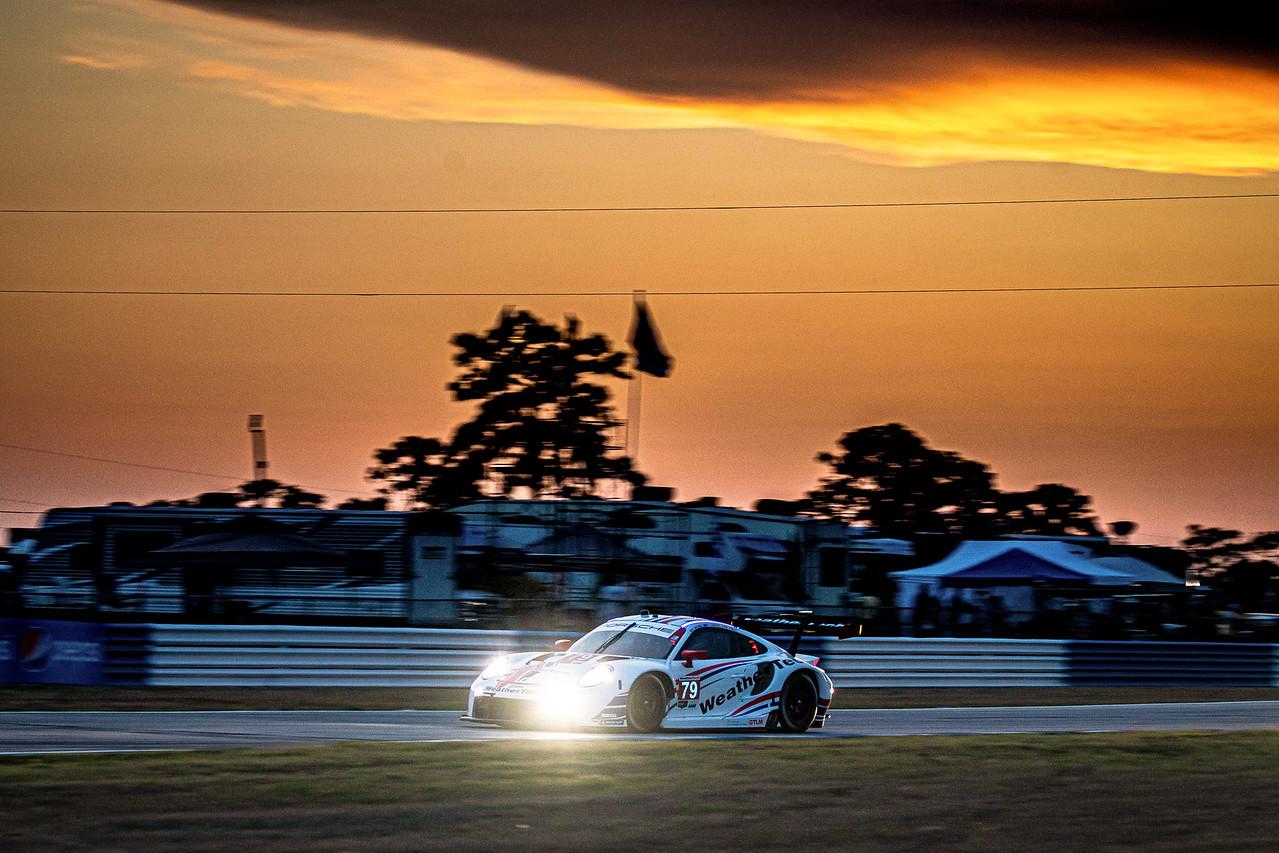 Porsche rounding a turn at sunset.