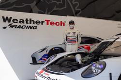 Cooper standing with Porsche.