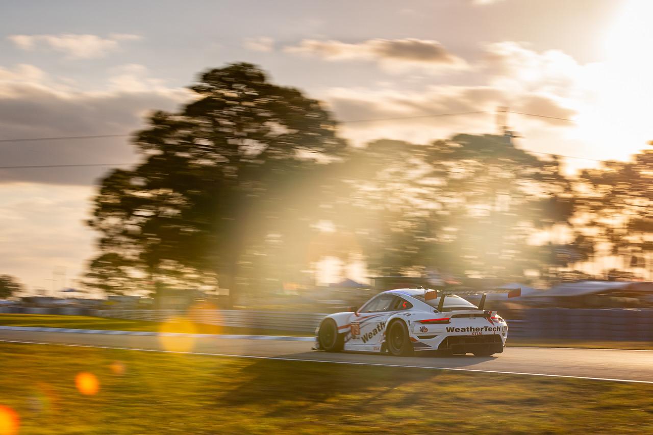 Porsche through the trees at sunrise.