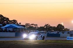Porsche racing at sunset.