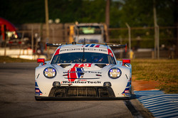 Porsche on track at sunrise.