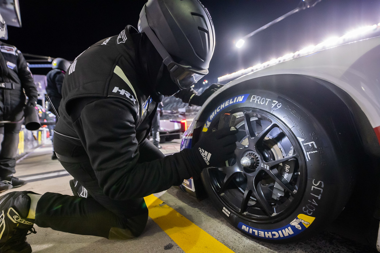 Pit crew changing a tire.