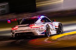 Porsche rounding a turn at night.