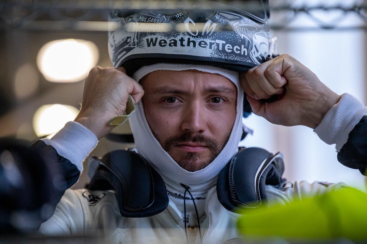 Cooper adjusting the racing helmet.