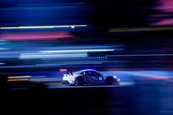 Porsche under the lights at night.