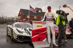 Cooper standing by Ferrari after win.