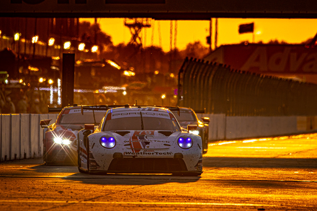 Porsche racing on track during sunset.