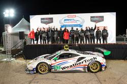 Ferrari with team on podium.