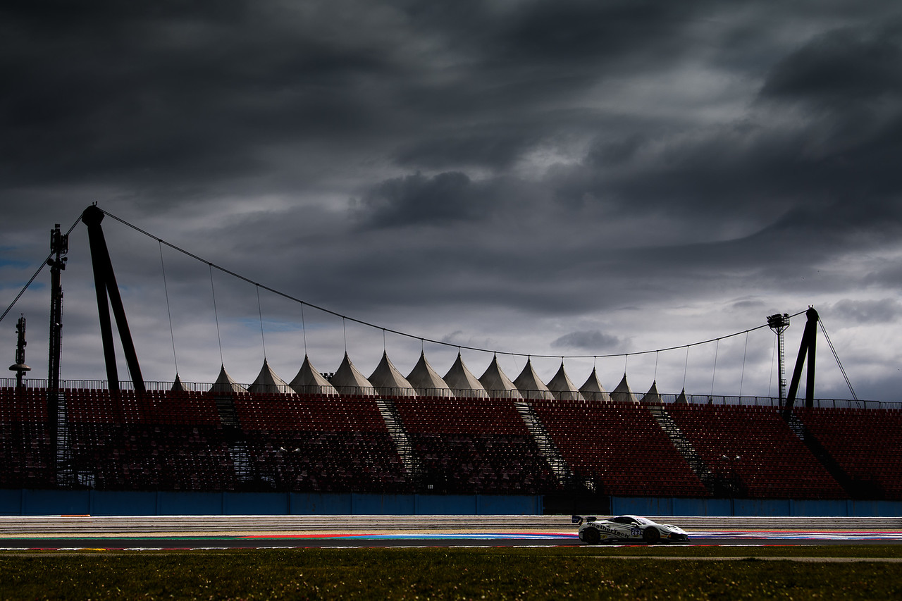 Rainy skies as the Ferrari drives past the grand stands.