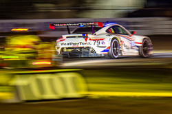 Porsche racing on the track at night.