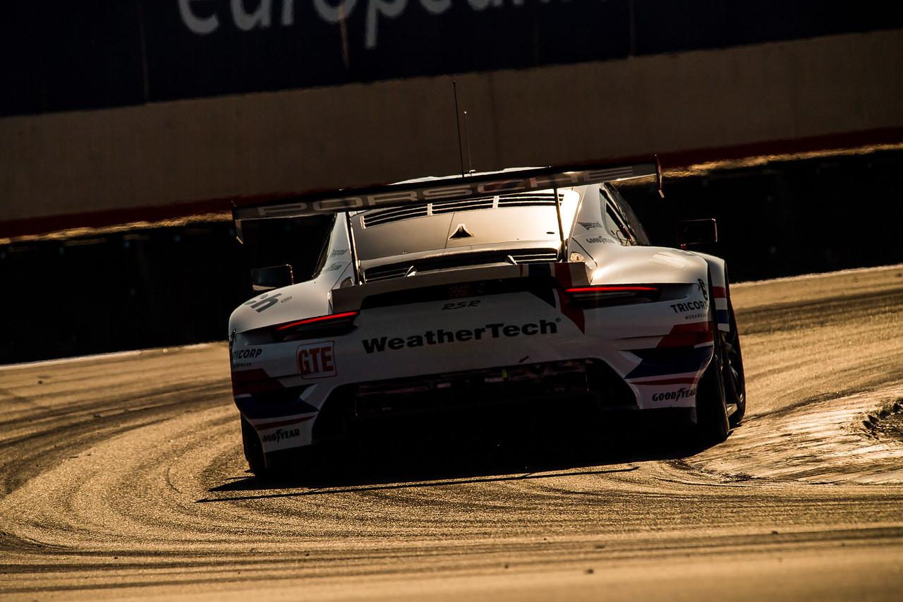 Porsche hugging a turn at sunrise.