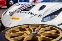 Close up on Ferrari wheel and hood.