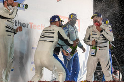 Team on the podium with champagne.