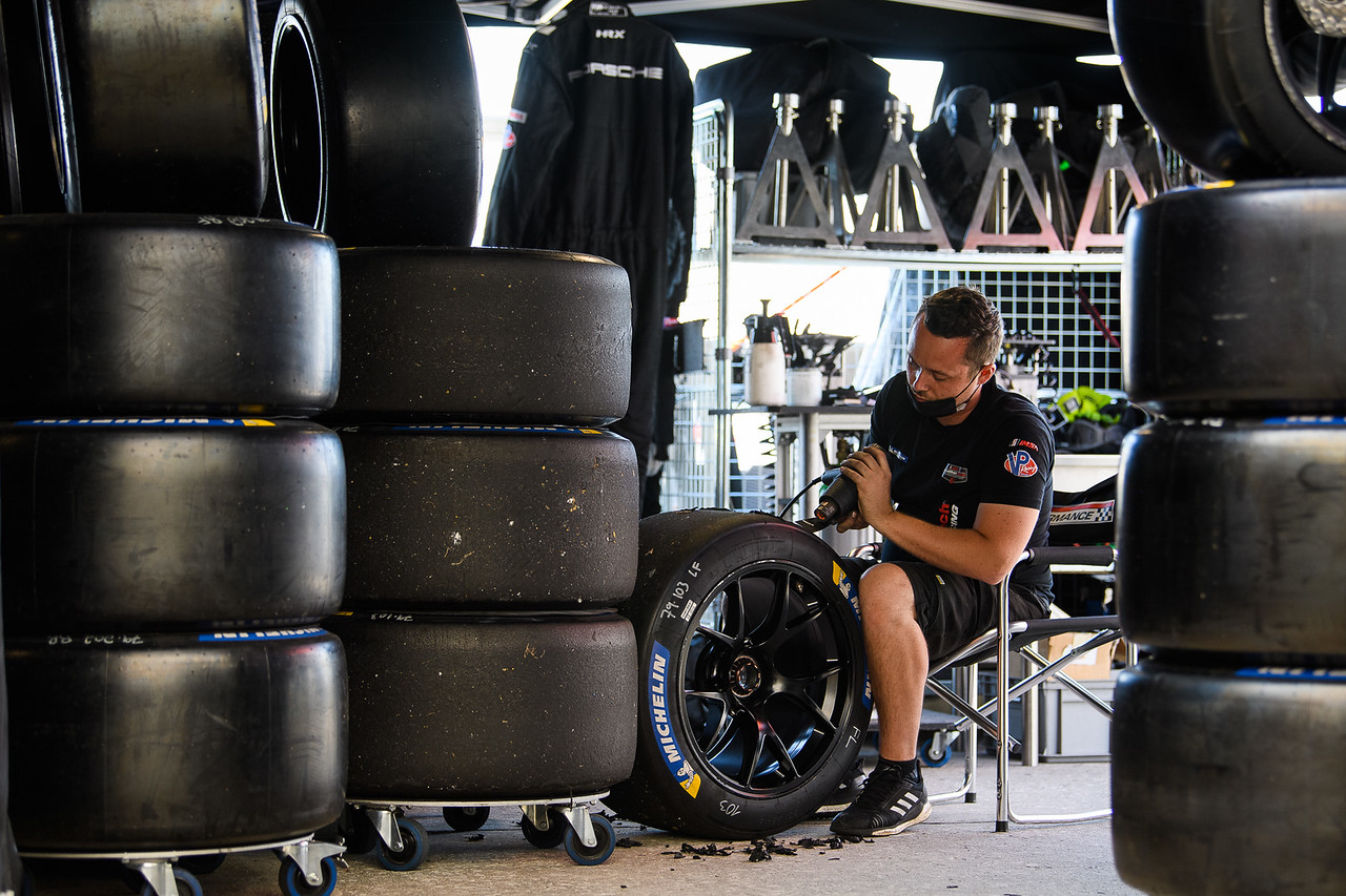 Crew member working on tires.