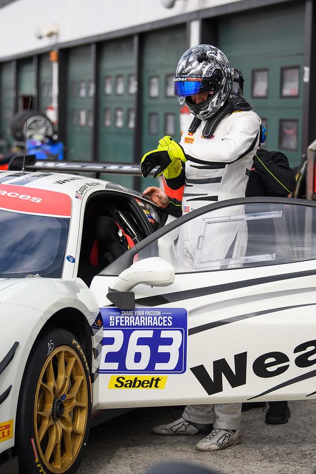Cooper standing by the Ferrari.