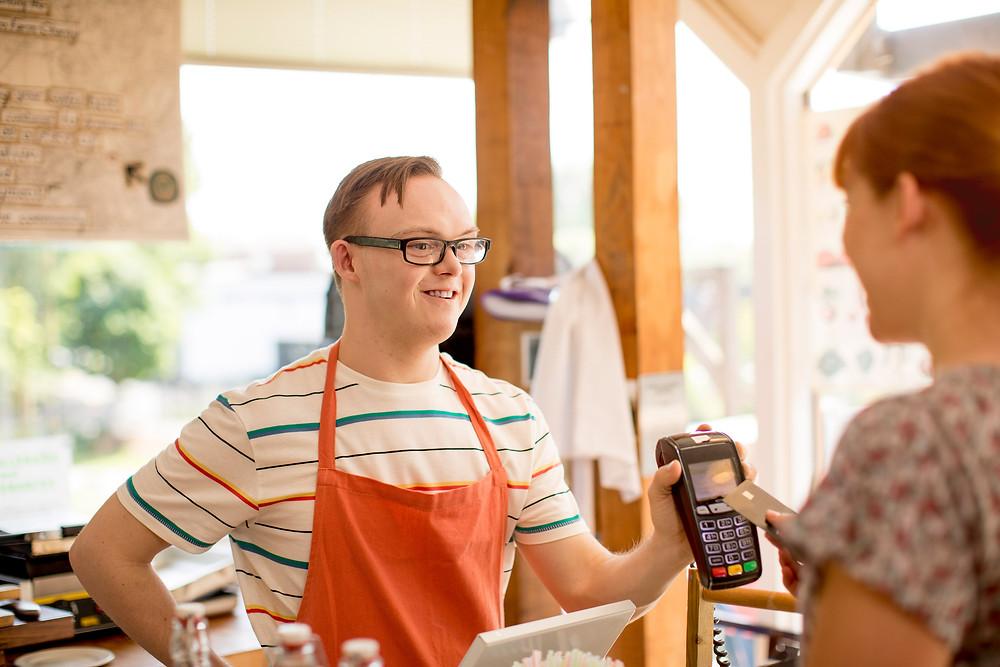 Se muestra a un trabajador con discapacidad intelectual usando un delantal de color naranja, como parte del uniforme de un café y está atendiendo amablemente a una cliente