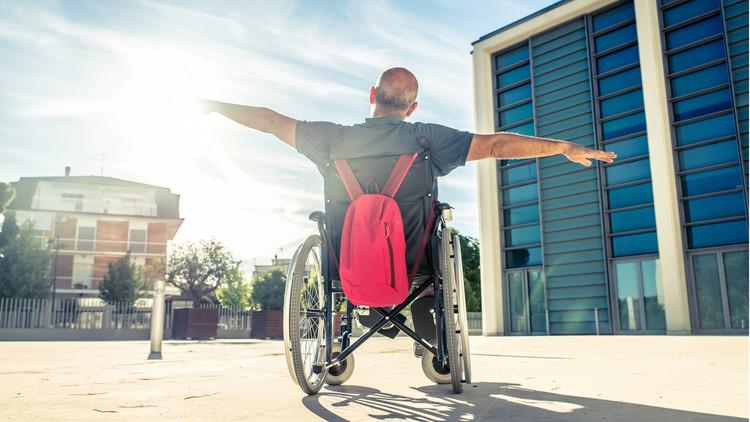 Un adulto mayor que se desplaza en sillas de ruedas y yiene sus brazos extendido, se nota como un hombre feliz y libre. El escenario de la fotografía se muestra en una empresa y el entorno se ve accesible y que cumple con el manual de accesibilidad universal