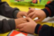 Manos de niños compartiendo en la escula