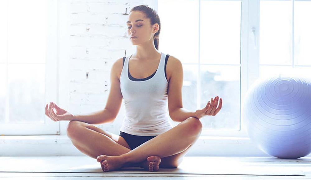 Mujer con discapacidad psíquica, sentada en el suelo haciendo posición de yoga