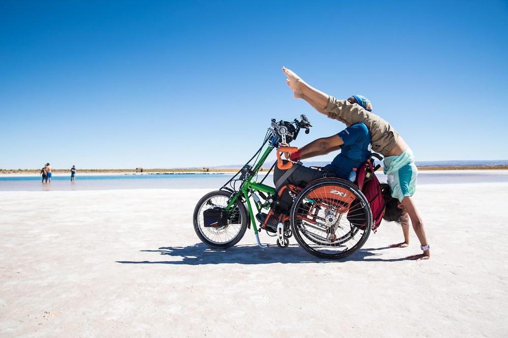 Escenario en la orilla de una playa, una mujer y un hombre en silla de ruedas realizando yoga adaptado
