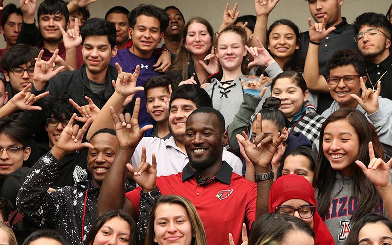"""El Atleta de Basquets Derrick Coleman rodeado de sus estudiantes sordos, haciendo la seña de """"Te quiero"""" o """"I Love You"""""""