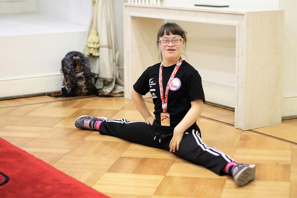 Se muestra la foto de paola en en posción de estiramiento sentada en el suelo, sonriendo y con su medalla ganada en el mundial.