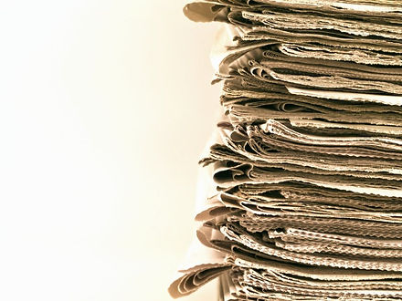 depositphotos_5118563-stock-photo-old-newspapers-stacked-from-the_edited.jpg