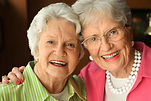 A picture of twi white haired white women smiling. One of the women embraces the other.