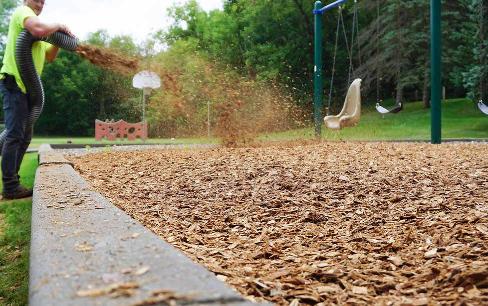Action photo of engineered wood fiber being blown into playground