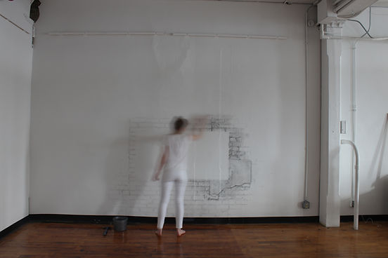 A person wearing all white stands in front of a white wall with bricks drawn onto it. The person in all white is erasing the drawing.