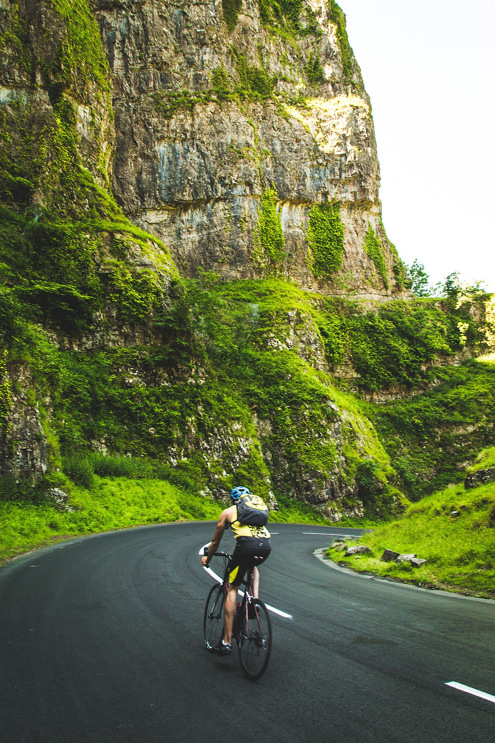 man bicycling by himself on a mountain road
