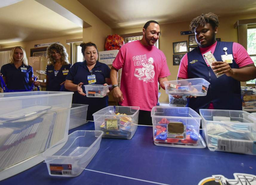 Charlie Batch packs backpacks with Walmart employees.