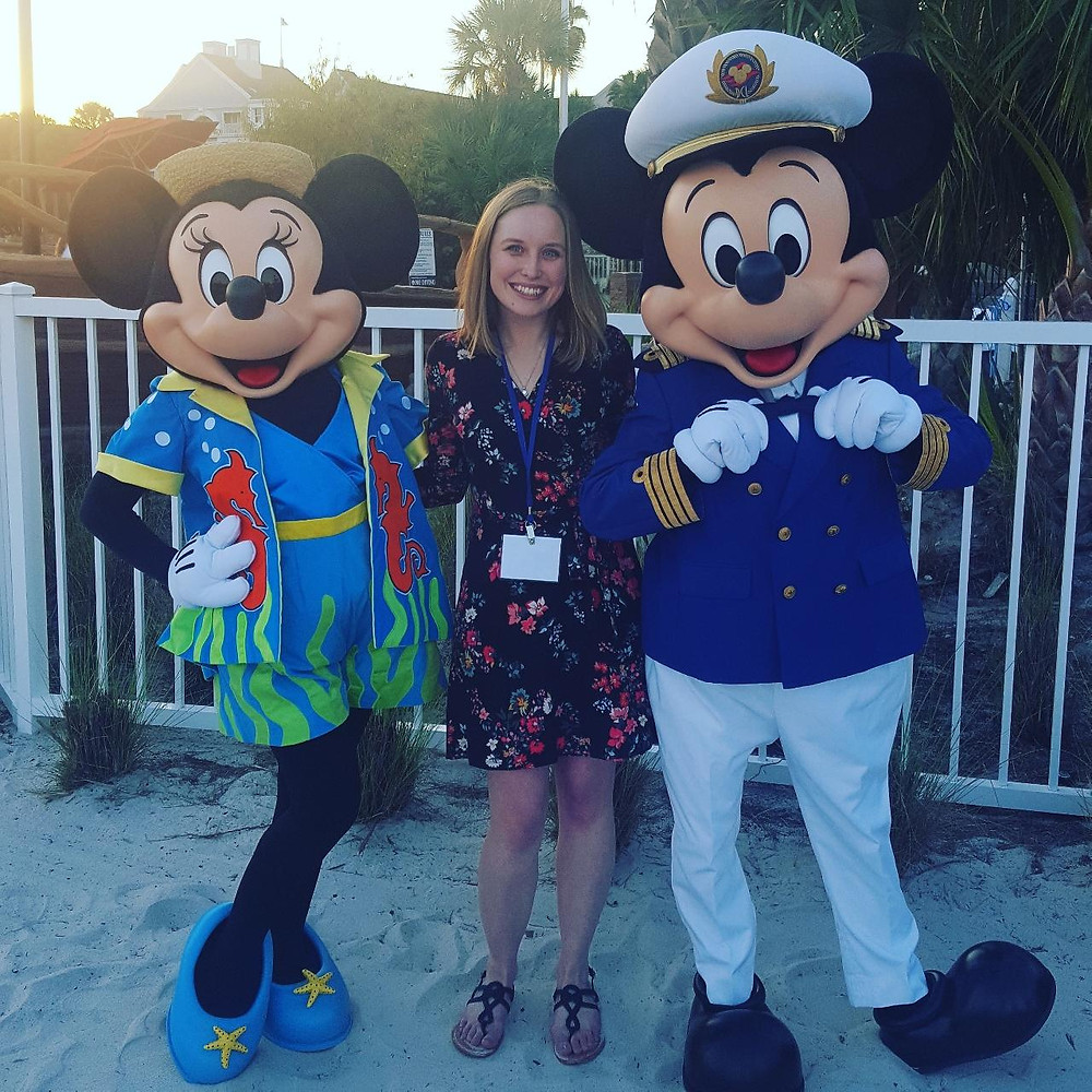 Elizabeth Stoner posing for a photo with Minnie and Mickey Mouse