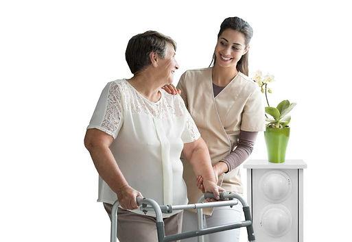 Hoitaja ja ikääntynyt asiakas seisovat Seniortek Oy:n kukkatolpan edessä hymyillen