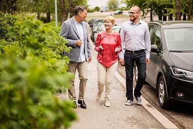 Kolme aikuista kävelee kadulla ja keskustelee