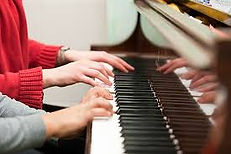 piano teacher and student playing piano together