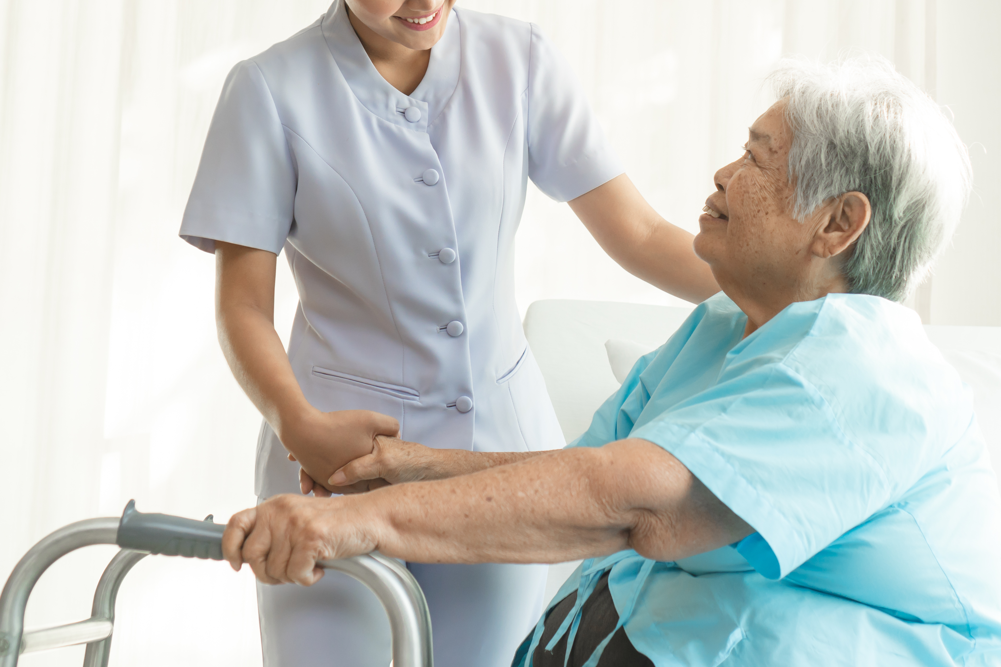 Cheerful asian nurse visiting elderly pa